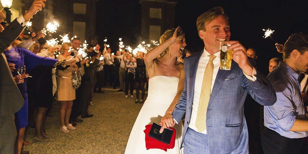 Bruidspaar loopt door een sterretjeshaag.