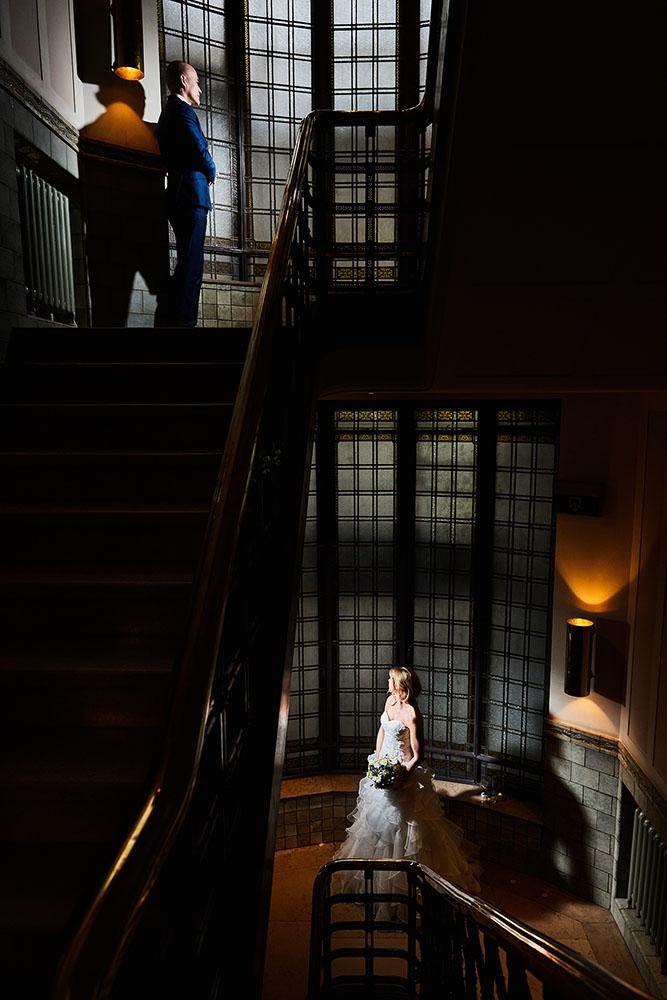 Het bruidspaar wordt gefotografeerd bij een donkere trap.