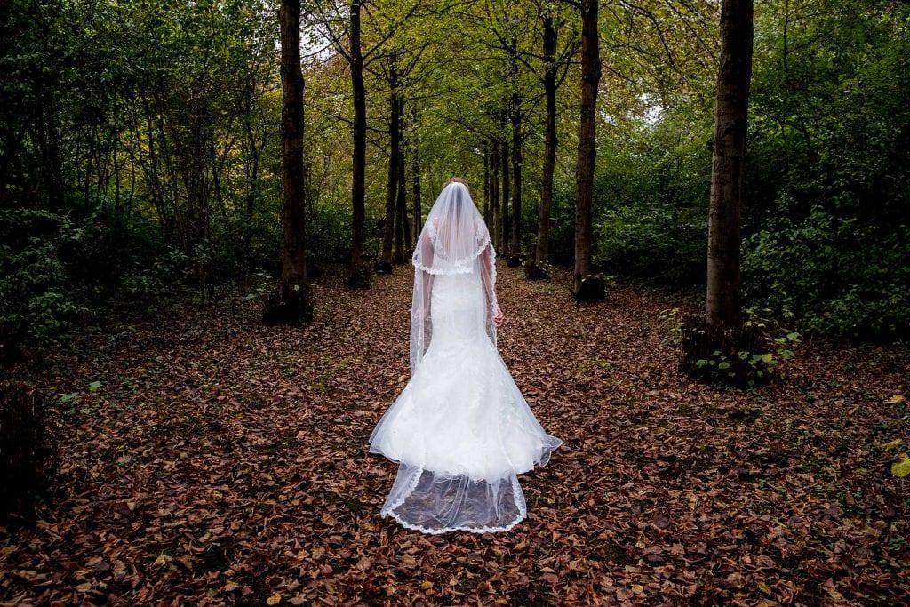 Bruid met sluier loopt door bladeren in de herfst