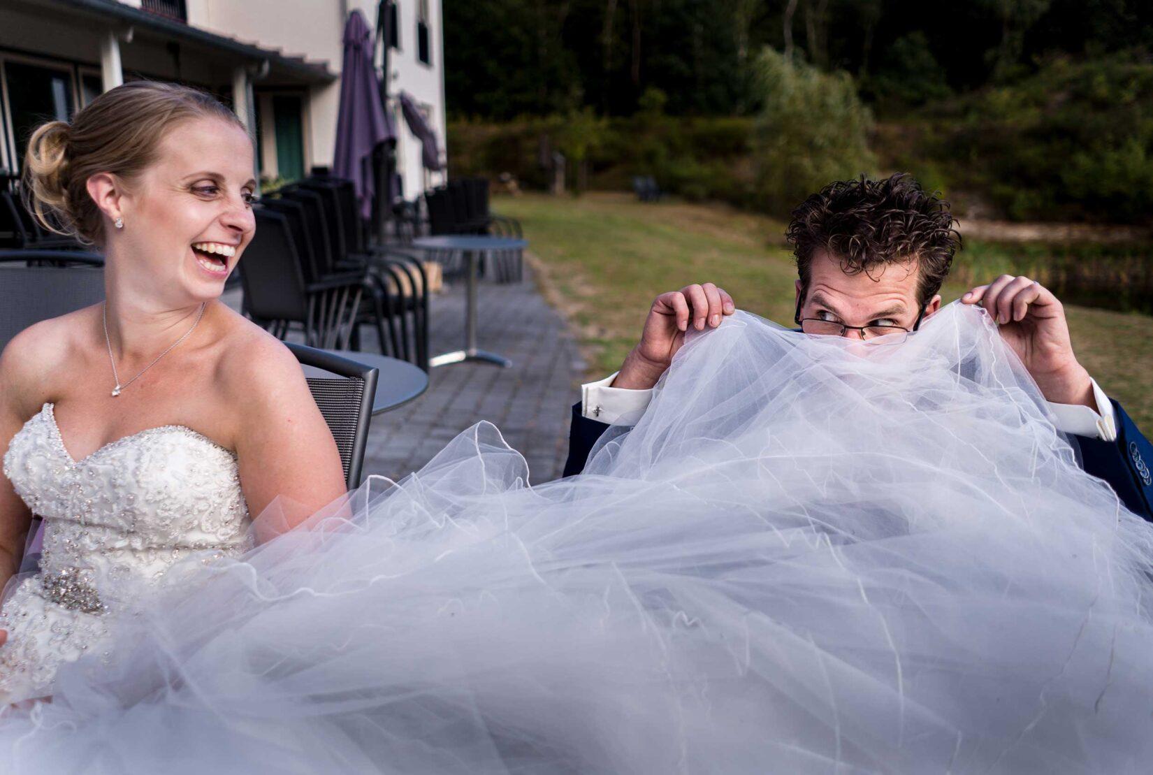 Bruidegom verstopt achter de bruidsjurk