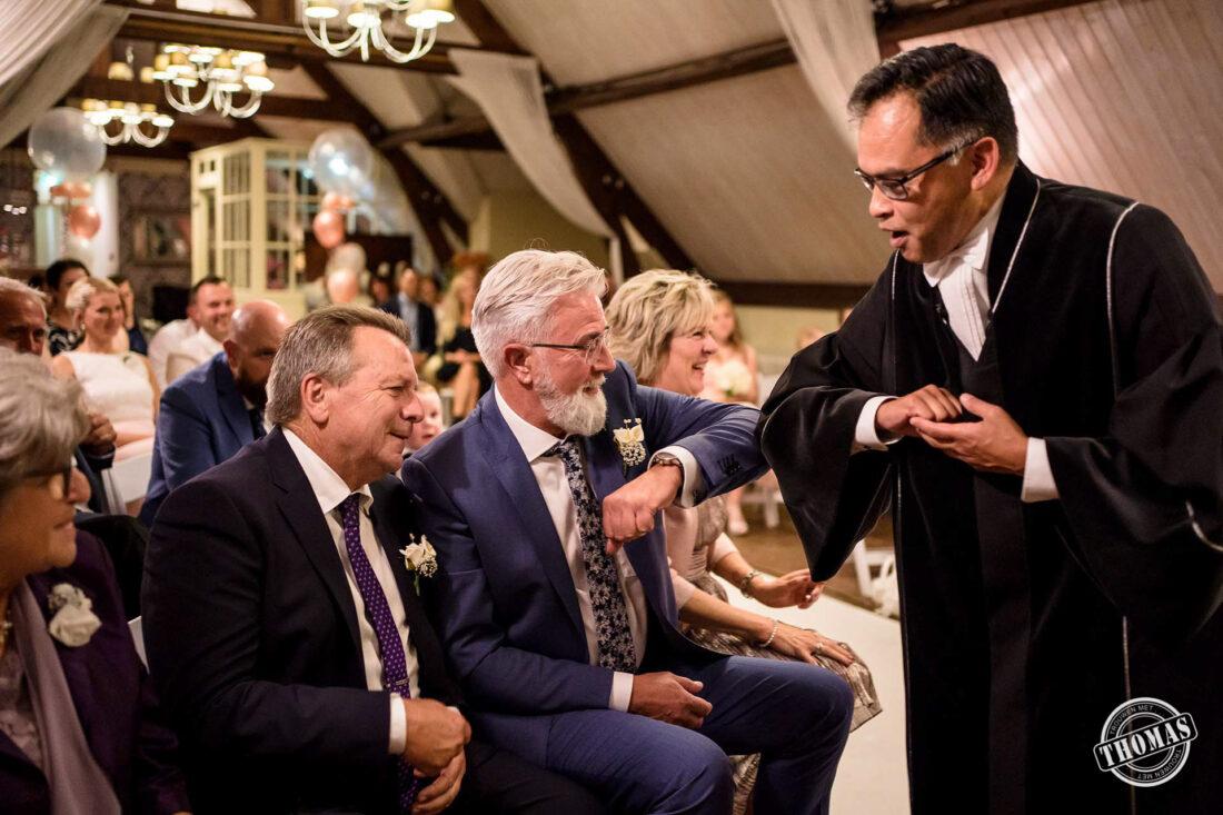 De vader van de bruid krijgt een elleboog groet van de ambtenaar.