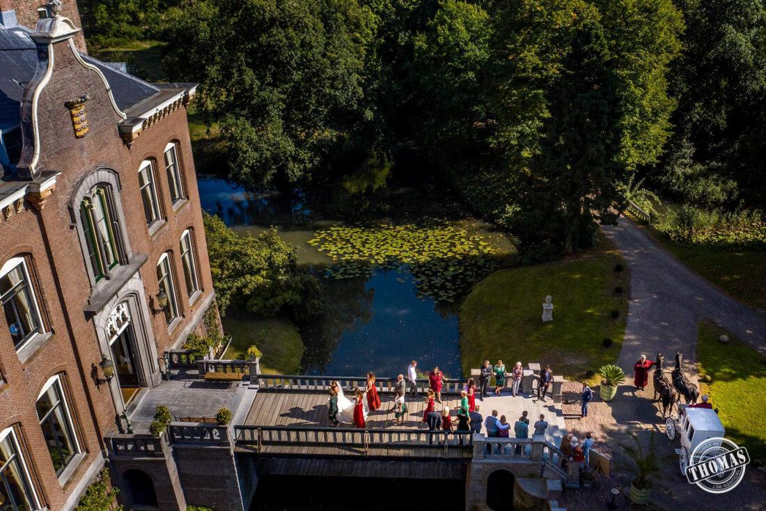 Het bruidspaar loopt over de brug van Kasteel Sterkenburg