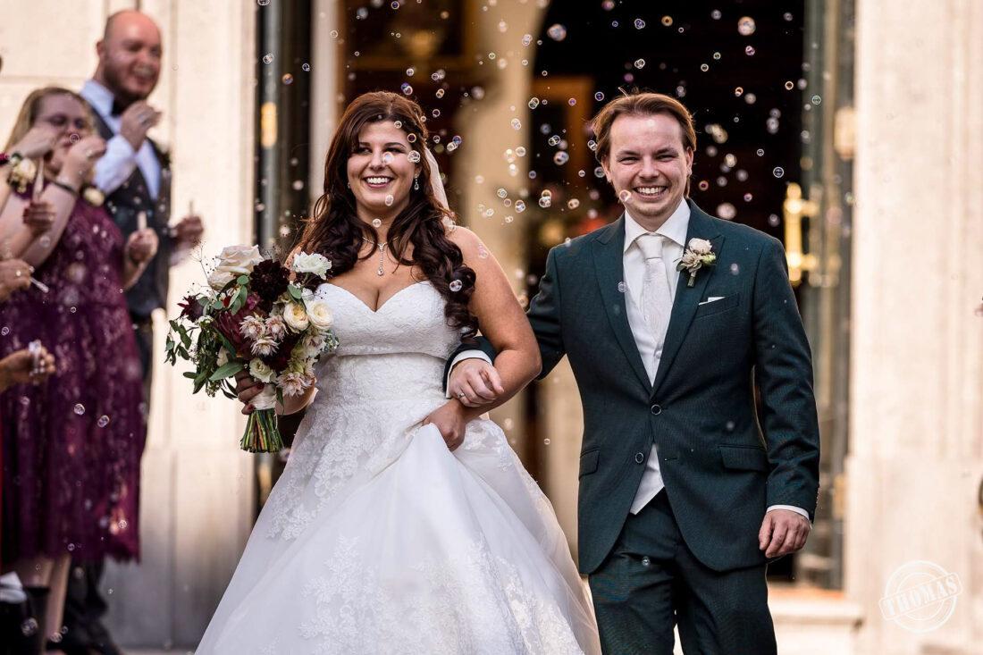 Bruidspaar loopt door bellenblaas haag.