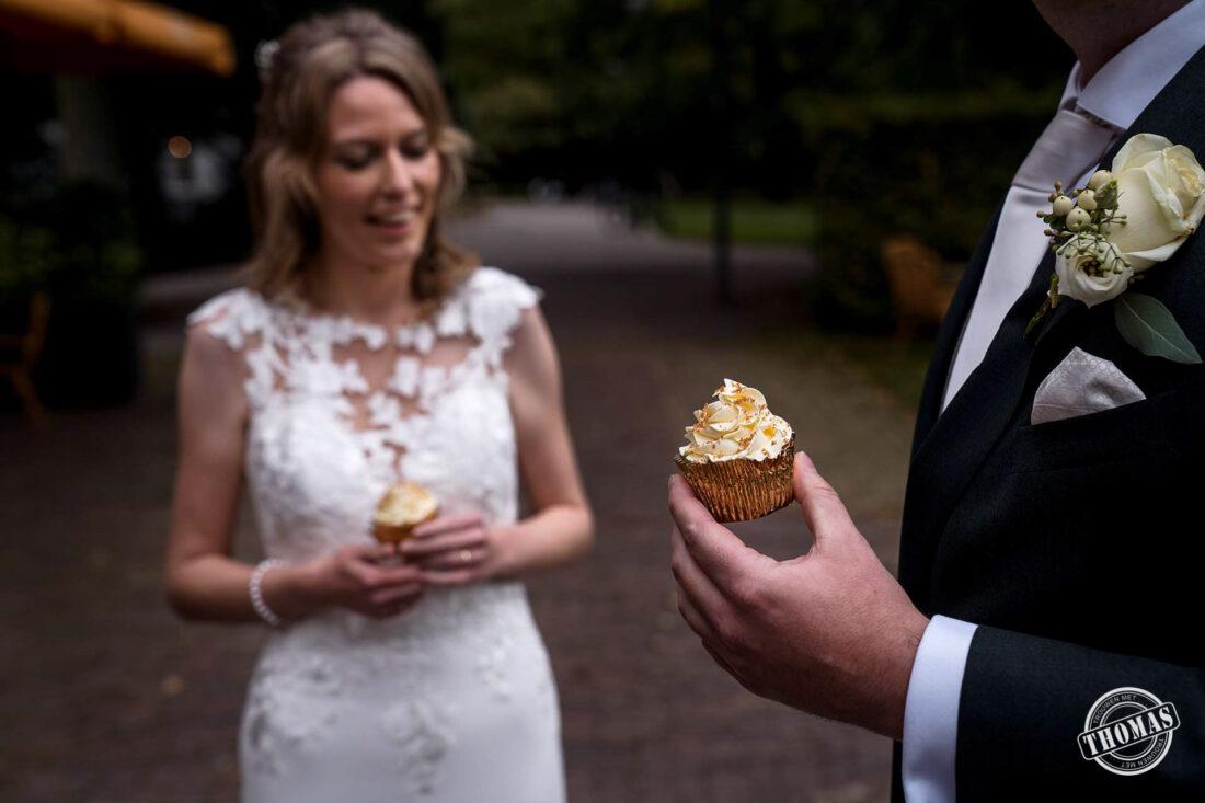 Bruid en bruidegom eten cupcake van sweettable