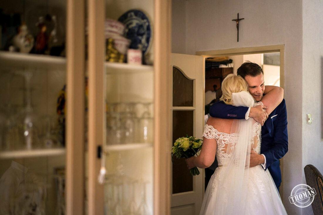 Bruid krijgt knuffel van familie.