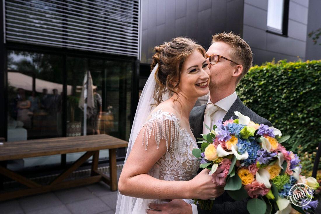 Bruidegom kust de bruid op haar wang.