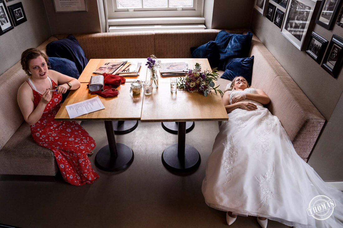Bruid neemt pauze tijdens groepsfoto's
