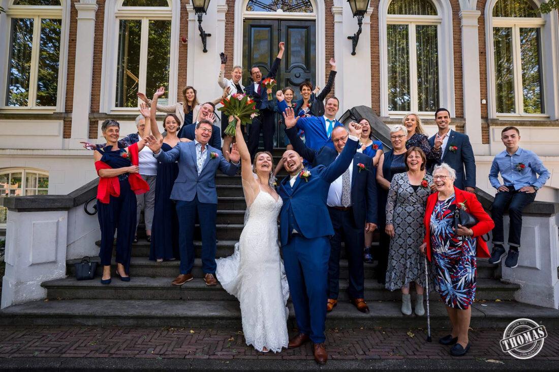 Groepsfoto met bruidspaar buiten op afstand
