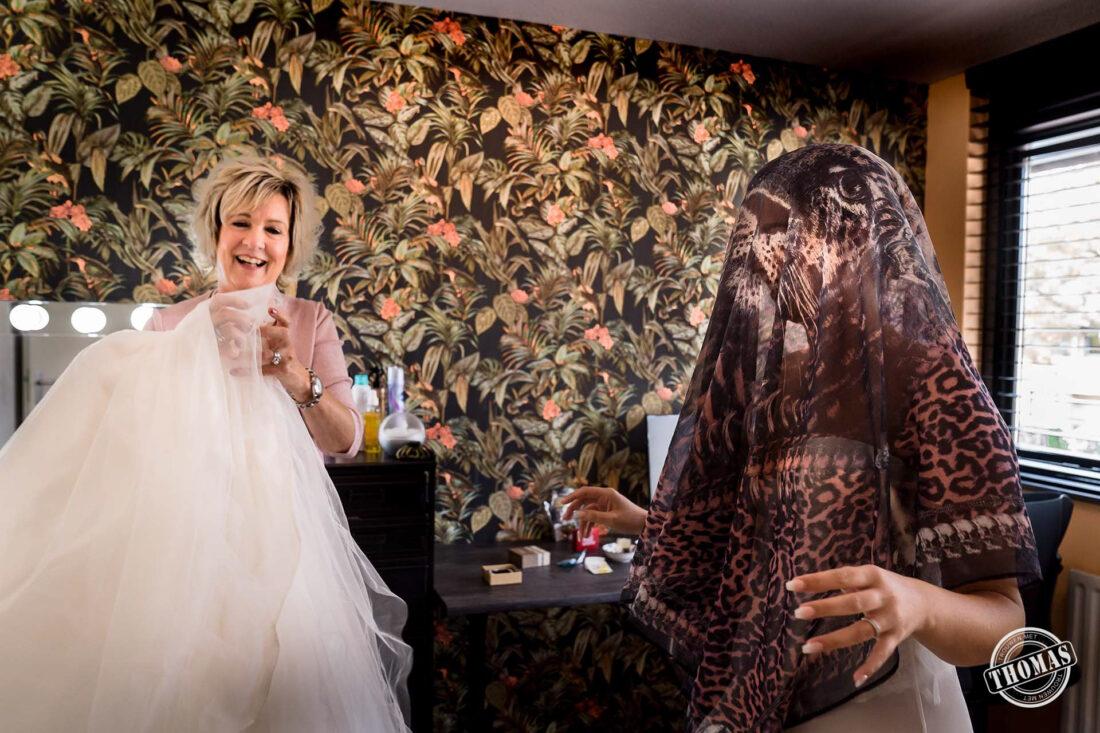 Bruid kleedt zich aan met doek over hoofd.