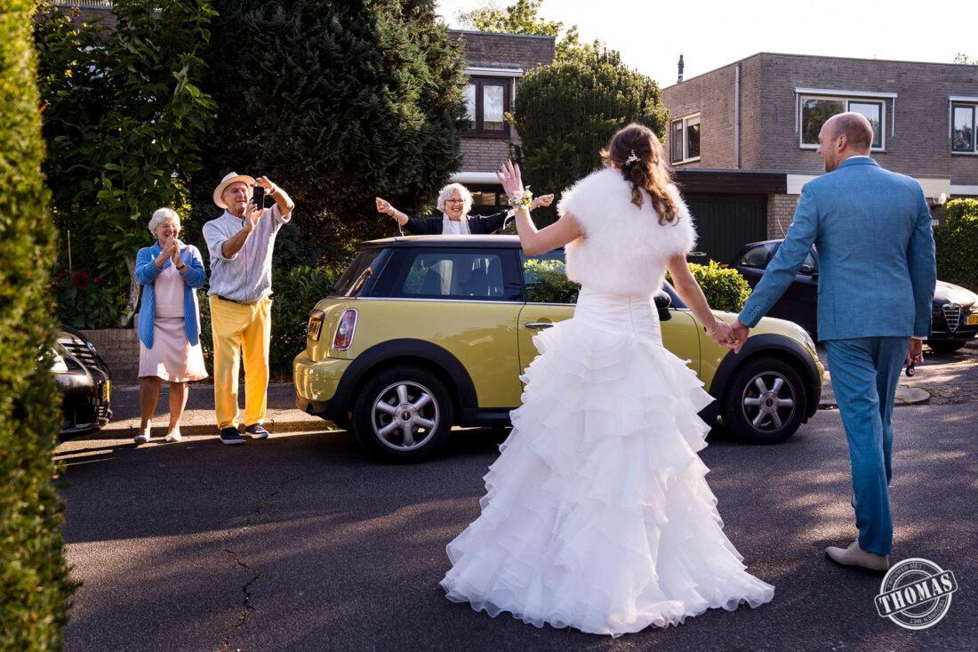 Bruidspaar wordt opgewacht door gasten.