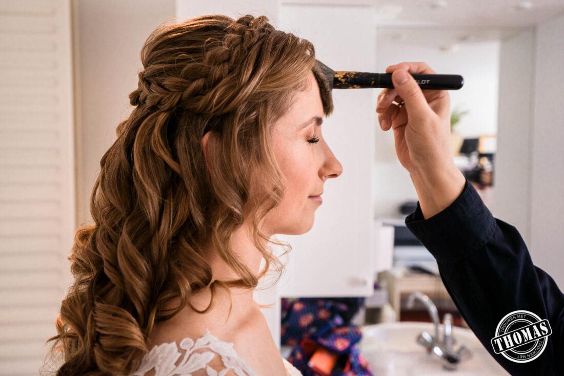 De bruid wordt gepoederd door de visagiste.